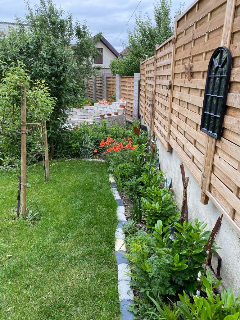 Grünbereich im Garten mit Holzzaun in Betonsteinpfeilern