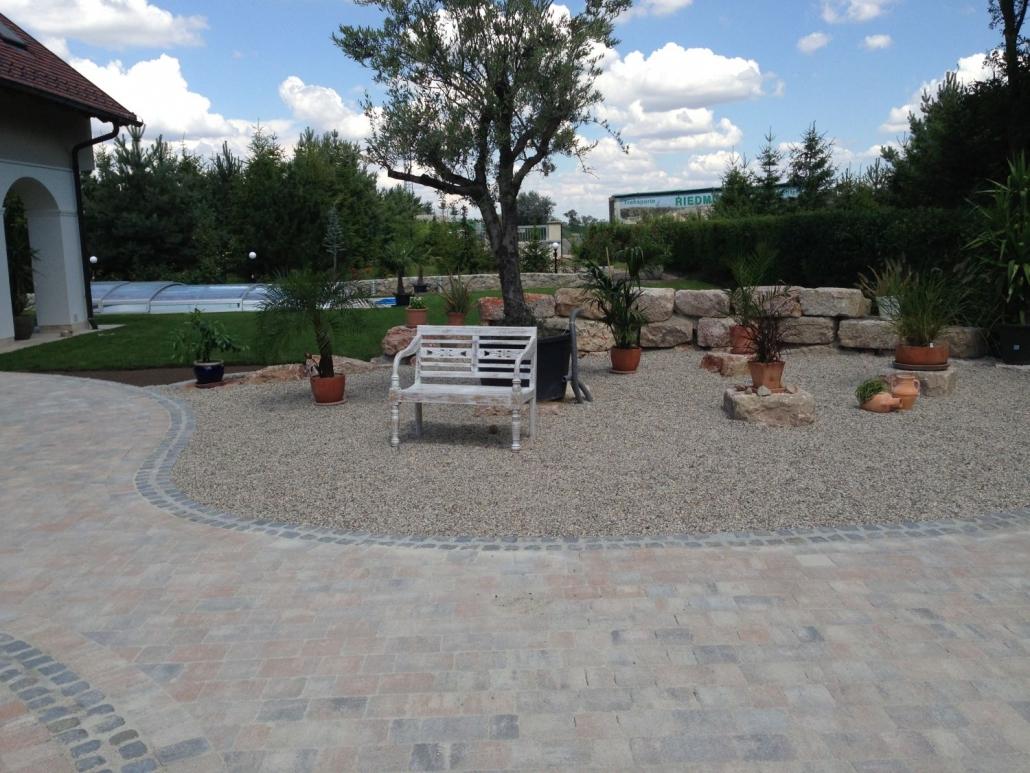 Plasterung mit verschiedenen Steinarten und Kiesplatz mit Sitzgelegenheit