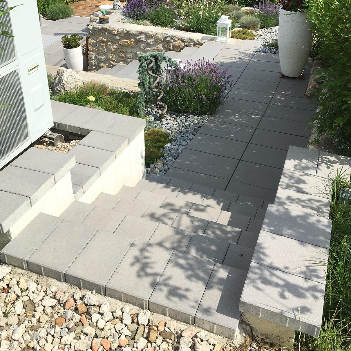 Betonsteintreppen mit Pflanzen und Natursteinmauern